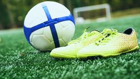 Soccer ball and football boots on green grass. Yellow soccer ball and football boots on green grass stock photography
