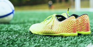Soccer ball and football boots on green grass. Yellow soccer ball and football boots on green grass royalty free stock photos