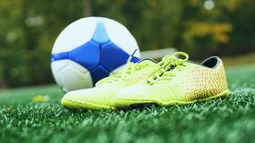 Soccer ball and football boots on green grass. Yellow soccer ball and football boots on green grass royalty free stock image