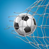 Soccer ball or football breaking through the net Stock Image