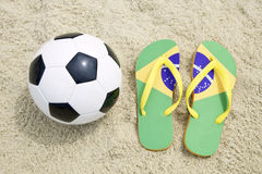 Soccer Ball Football and Flip Flops on Brazilian Beach Royalty Free Stock Photo
