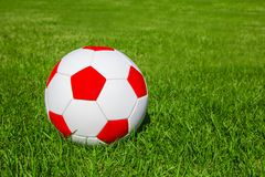 Soccer ball or football ball on green field. White and red soccer ball on fresh green meadow/ grass, copy space for text, concept football Royalty Free Stock Photography