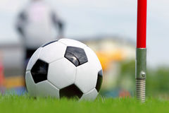 Soccer ball on football green field on the corner Stock Photography