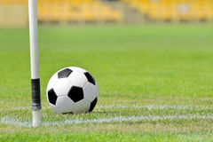 Soccer ball on football green field on the corner Stock Images