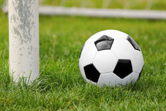 Soccer ball on football green field with gate Stock Images