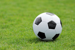 Soccer ball on football green field with space for text Stock Images