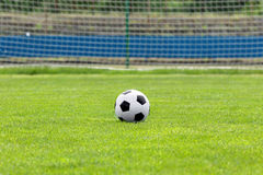 Soccer ball on football green field with space for text Royalty Free Stock Photos