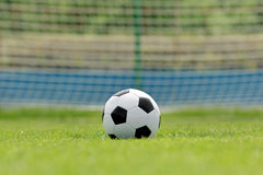 Soccer ball on football green field with space for text Royalty Free Stock Image