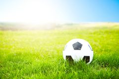Soccer ball or football ball on ground and green field of grass Stock Image