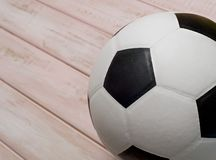 Soccer ball or football on pink wooden floor.  stock photography