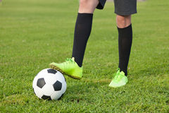 Soccer ball and a football player  legs on a green lawn, close-u Stock Photos