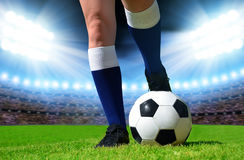 Soccer ball and foots of football player Stock Images