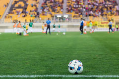 Soccer ball in the foreground and blurred players Stock Photos