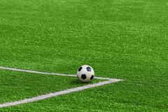 A soccer ball framed by white corner markings on a green footbal Royalty Free Stock Photo