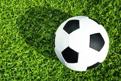 Soccer ball on fresh green football field grass, top view. Space for text royalty free stock photos