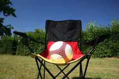 Soccer ball on a german flagged chair. Soccer ball in front of a german flagged chair stock photography