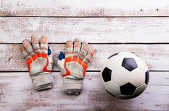 Soccer ball, gloves on white wooden floor, studio shot Royalty Free Stock Images