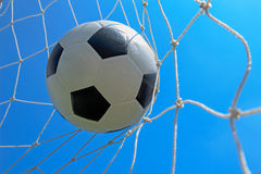 Soccer ball in goal and blue sky Stock Images