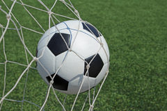 Soccer ball in goal and green grass field. Background Royalty Free Stock Photo
