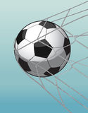 Soccer ball in goal net on the blue background. Royalty Free Stock Image