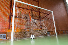 Soccer ball in a goal post. Low angle view of a soccer ball in a goal post on an all weather green indoor court in a brick building Stock Photography