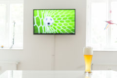 Soccer ball in the goal on television and a glass of wheat beer on a table Royalty Free Stock Photos