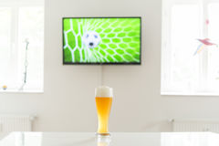 Soccer ball in the goal on television and a glass of wheat beer on a table Stock Images