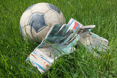 Soccer ball and goalkeeper gloves on grass Royalty Free Stock Images