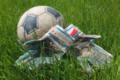 Soccer ball and goalkeeper gloves on grass Stock Photos