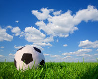 Soccer ball in grass. Soft Soccer ball in grass and blue cloudy sky Royalty Free Stock Photography