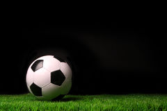 Soccer ball on grass against black Stock Photos