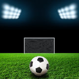 Soccer ball on grass against black background Royalty Free Stock Photo