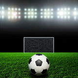 Soccer ball on grass against black background Royalty Free Stock Images