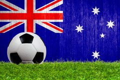 Soccer ball on grass with Australia flag Stock Photos