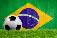 Soccer ball on grass with Brazil flag background. Close up royalty free stock photography