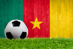 Soccer ball on grass with Cameroon flag background. Close up Royalty Free Stock Photography
