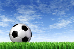 Soccer Ball and grass Field background. With a blue sky and green european football stadium turf as a concept of fun summer team  leisure sport for players who Royalty Free Stock Photo