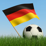 Soccer ball in the grass and flag of Germany. Soccer ball in the grass and the flag of Germany against the blue sky. 3d Royalty Free Stock Image