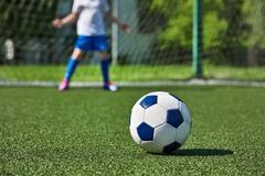 Soccer ball on grass and football boy at gate keeper. Soccer ball on the green lawn of the stadium and the football boy at the gate keeper royalty free stock photos