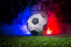 Soccer ball on grass with France flag with smoke and lights. Soccer concept. royalty free stock photos