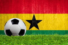 Soccer ball on grass with Ghana flag background Stock Images