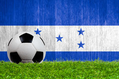 Soccer ball on grass with Honduras flag background Stock Images