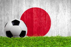 Soccer ball on grass with Japan flag background Royalty Free Stock Photos