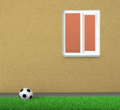 Soccer ball on a grass near wall with window Stock Image