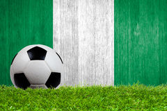 Soccer ball on grass with Nigeria flag background Stock Images