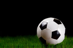 Soccer ball on grass over black. Background Royalty Free Stock Photo