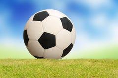 Soccer ball on grass sky background. Soccer ball on green grass sky background stock photos
