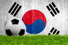 Soccer ball on grass with South Korea flag. Background close up royalty free stock image