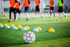 Soccer ball on green artificial turf with blurry of maker cones. And player training. Soccer academy royalty free stock photos