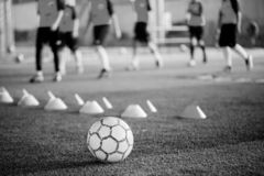 Soccer ball on green artificial turf with blurry of maker cones and player training. Black and white picture of Soccer ball on green artificial turf with blurry royalty free stock photos